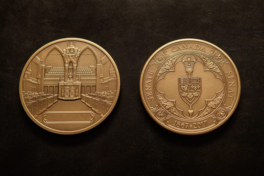 The Senate 150th Anniversary Medals feature the Senate's badge on the front and the Senate Chamber on the reverse. (Photo Credit: Greg Kolz)