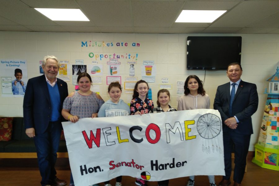 Senator Brian Francis (left) and students at Mount Stewart Consolidated School welcome Senator Peter Harder to Prince Edward Island.